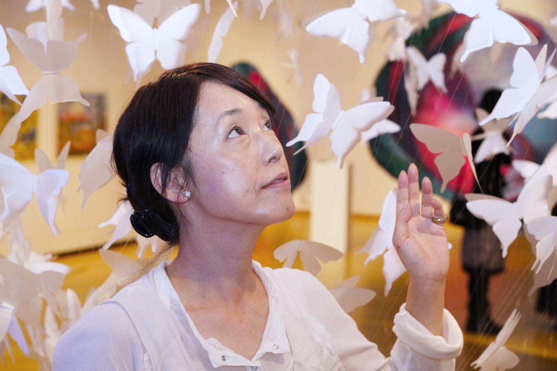Porträtt på en person med pappersfjärilar runtomkring
