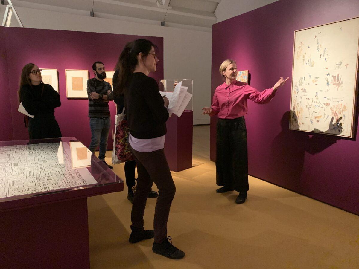 Personer som ser utställning i ett rosa rum